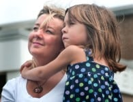 Tonya Schevers holds her daughter, Marlee Schevers, 7, during a ceremony commemorating the fifth anniversary of Hurricane Katrina Aug. 29, 2010 in Gulfport, Miss. The scope of the disaster after the hurricane changed the way faith-based organizations handle disaster response, with many moving toward a more holistic approach. (Photo by Carmen K. Sisson/Cloudybright)