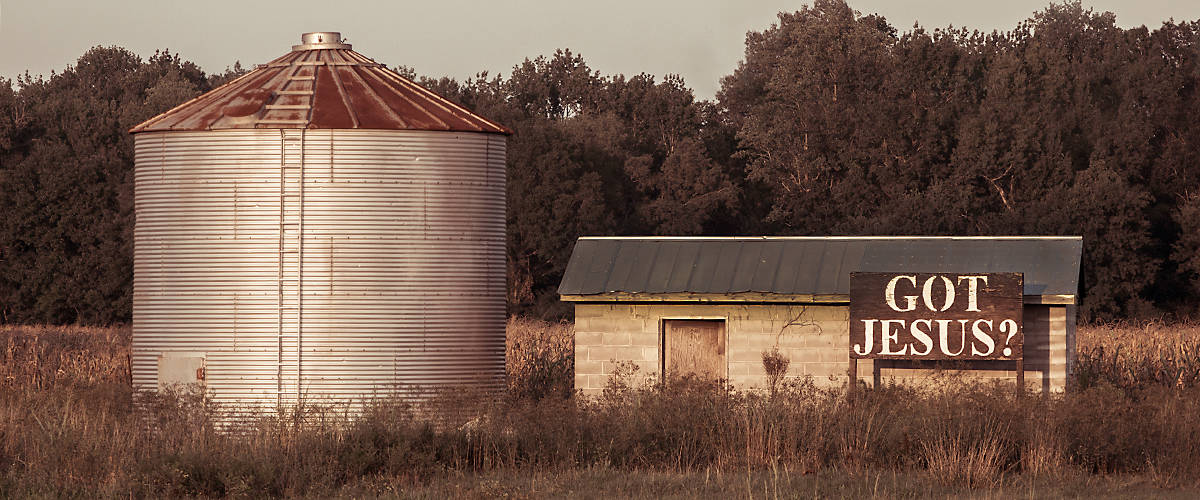 "A grain silo stands beside an abandoned shed featuring a ""Got Jesus?"" sign in Monroe County, Mississippi. (Photo by Carmen K. Sisson/Cloudybright)"