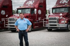 Michael Massengill, president of Big M Transportation, poses with the company's new Mack trucks at the company headquarters in Blue Mountain, Mississippi. (Photo courtesy of Big M Transportation)