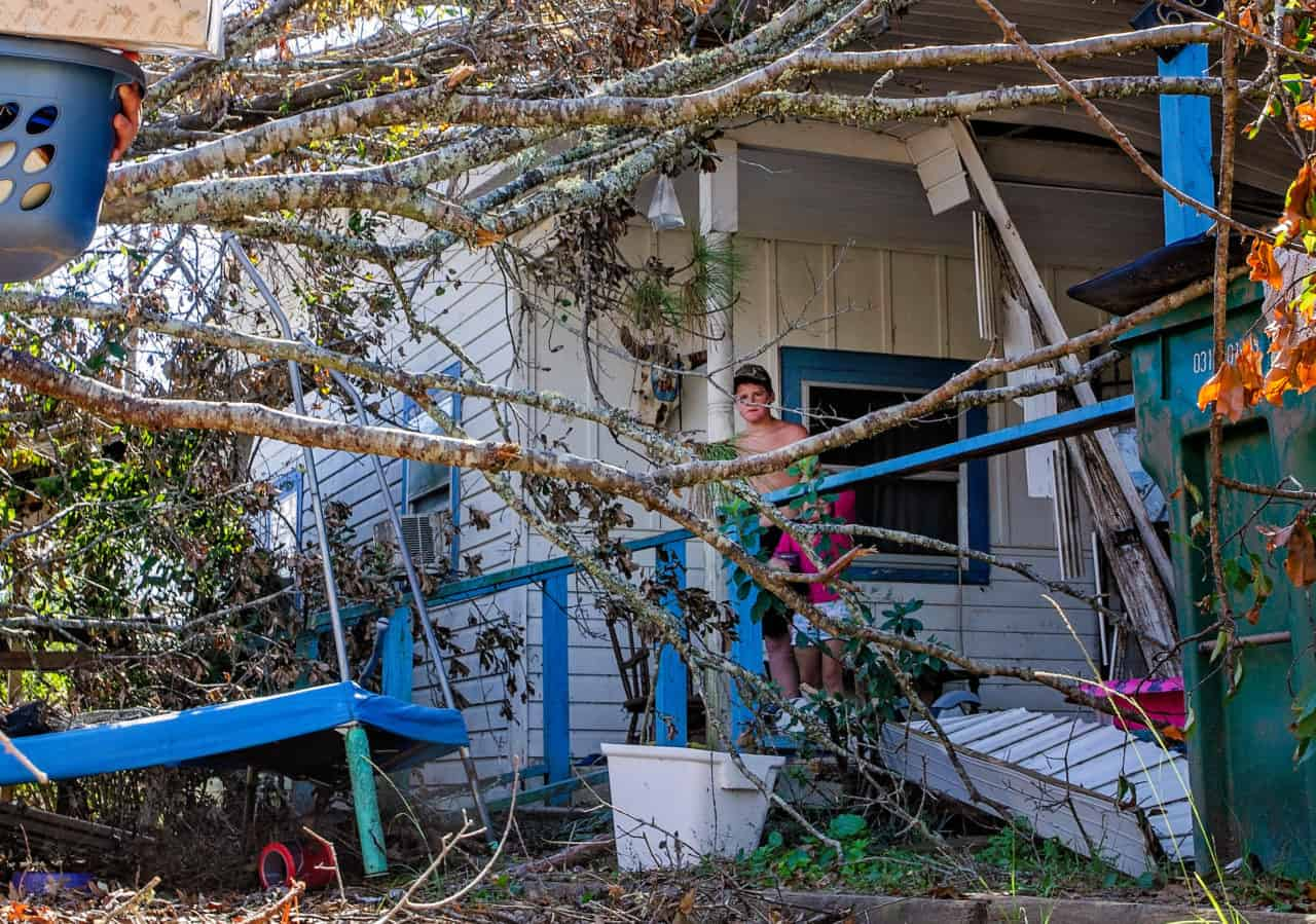 Jayden Davis, 14, watches as his brother carries their belongings from their destroyed home, Oct. 21, 2018, in Grand Ridge, Fla. Davis and his family had to move after Hurricane Michael swept through the area Oct. 10, 2018, leaving behind a swath of destruction across the Florida Panhandle and parts of Alabama and Georgia. (Photo by Carmen K. Sisson/Cloudybright)