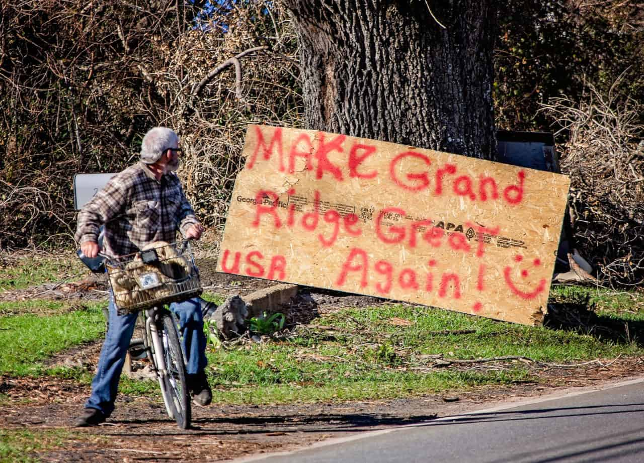 "John Holland, 61, stops to look at a handpainted sign entreating passersby to ""Make Grand Ridge Great Again,"" Oct. 21, 2018, in Grand Ridge, Fla. Holland lost his front porch and one of his favorite bicycles when Hurricane Michael swept through the area Oct. 10, 2018, leaving behind a swath of destruction across the Florida Panhandle and parts of Alabama and Georgia. (Photo by Carmen K. Sisson/Cloudybright)"